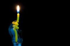 Gul stearinljus i en bruten ljus kula royaltyfria bilder