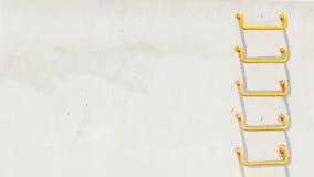 Gul stege på ljus - grå conrecetevägg arkivfoto