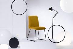Gul stol f?r stilfull sammet bredvid den h?gv?xta industriella svarta lampan i den vita inre royaltyfri fotografi