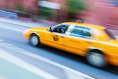 Gul taxi i NYC i rörelsesuddighet Royaltyfria Bilder