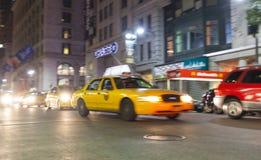 Gul taxi på natten i New York City i rörelsesuddighet Royaltyfri Bild