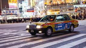 Gul taxispring till och med den Shibuya korsningen royaltyfri bild
