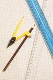 Gul teckningskompass med svart pensil och linjaler på grafPA Fotografering för Bildbyråer