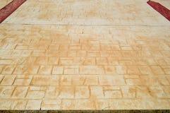 Gul textur av en gammal forntida tegelstentegelplatta med sömmar på golvet med bruna remsor Arkivfoto