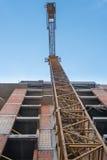 Gul tornkran och byggnadskonstruktion royaltyfria foton