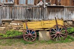 Gul träwaggon framme av det gamla huset i den Jeravna byn royaltyfri foto