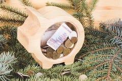 Gul tr?spargris med mynt och sedlar f?r ryssrubel Träbakgrund för jul och nytt års med filialer av royaltyfria foton