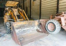 Gul traktor som parkeras i garaget. Royaltyfria Bilder
