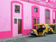 Gul tuktuk vid den rosa byggnadshavannacigarren, Kuba Royaltyfri Foto