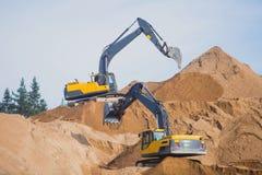 Gul tung grävskopa och bulldozer som gräver sand och arbete under vägarbeten och att lasta av sand och vägmetall Royaltyfria Bilder