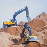 Gul tung grävskopa och bulldozer som gräver sand och arbete under vägarbeten och att lasta av sand och vägmetall Arkivfoton
