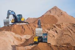 Gul tung grävskopa och bulldozer som gräver sand och arbete under vägarbeten och att lasta av sand och vägmetall royaltyfri foto
