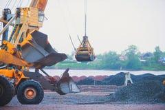 Gul tung grävskopa och bulldozer som gräver sand och arbete under vägarbeten och att lasta av sand och vägmetall Fotografering för Bildbyråer