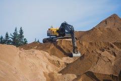 Gul tung grävskopa och bulldozer som gräver sand och arbete under vägarbeten och att lasta av sand och vägmetall under tankeskape Fotografering för Bildbyråer