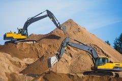 Gul tung grävskopa och bulldozer som gräver sand och arbete under vägarbeten och att lasta av sand och vägmetall under tankeskape Royaltyfria Bilder