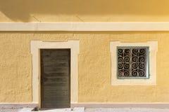 Gul vägg med dörren och fönstret Arkivbilder