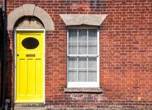Gul ytterdörr av ett gammalt traditionellt engelska terrasserat hus royaltyfria foton