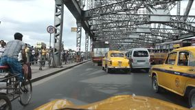 Gula ambassadörtaxitaxiar går på den Howrah bron, Kolkata (Calcutta) Indien lager videofilmer