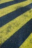 Gula band på asfalt arkivbilder