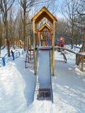 Gula barns glidbana i snön parkerar område av ‹för †staden Arkivbild