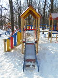 Gula barns glidbana i snön parkerar område av ‹för †staden Arkivfoto