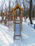 Gula barns glidbana i snön parkerar område av ‹för †staden Arkivfoton
