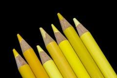 7 gula blyertspennor - svart bakgrund Fotografering för Bildbyråer