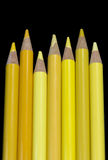 7 gula blyertspennor - svart bakgrund Arkivfoton
