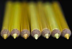 7 gula blyertspennor - svart bakgrund Royaltyfri Bild