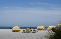 Gula cabanas och stolar på stranden Arkivfoto