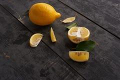 Gula citroner och sidor på tabellen Royaltyfria Bilder
