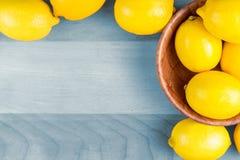 Gula citroner på det blåa wood brädet Royaltyfri Foto