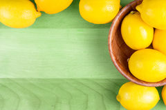 Gula citroner på det gröna wood brädet Fotografering för Bildbyråer