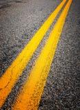 Gula delande linjer på huvudvägen Arkivfoto