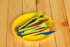 Gula disponibla plattor med kulöra plast- knivar, gafflar Royaltyfri Bild