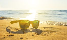 Gula exponeringsglas havssanden, solglasögon med härligt havslandskap solglasögon reflekteras i det guld- blöter sand som royaltyfri fotografi