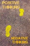 Gula fotsteg på trottoaren från negationen som tänker till det positiva tänkande meddelandet text för rest för bild för com-begre Royaltyfri Fotografi