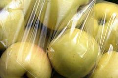 Gula guld- äpplen som packas i plast- film Arkivbilder
