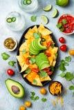 Gula havrenachoschiper med smältt ostsås, avokadot, jalapenoen, koriandersidor, tomatsalsa och den med is margaritan royaltyfri bild