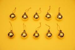 Gula julgranleksaker för orientering på gul bakgrund arkivfoton
