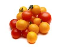 Gula körsbärsröda tomater som är röda och Arkivfoto