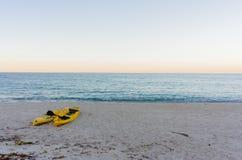 Gula kajaker på en sandig strand Arkivfoton