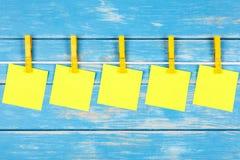 Gula klädnypor på ett rep med fem kort Arkivbilder