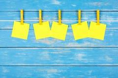 Gula klädnypor på ett rep med fem kort Arkivfoton