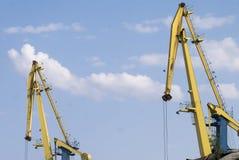 Gula marin- lastkranar mot blå himmel Royaltyfria Bilder