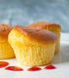 Gula muffin på en vit platta Arkivfoto