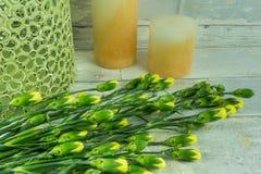 Gula nejlikor med stearinljus Royaltyfria Bilder
