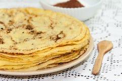 Gula nya pannkakor tjänade som på plattan med kakaosocker Royaltyfri Fotografi
