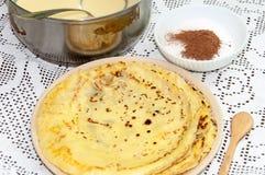 Gula nya pannkakor tjänade som på plattan med kakaosocker Arkivfoto
