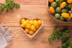 Gula och gröna körsbärsröda tomater i träbunkar fotografering för bildbyråer